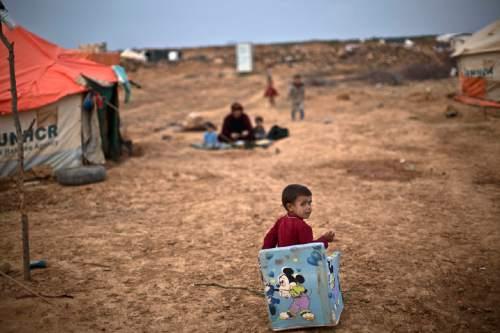 Syrian refugee boy Ahmad Faleh, 3, plays outside his family's tent at an informal settlement near the Syrian border on the outskirts of Mafraq, Jordan, Wednesday, Oct. 28, 2015. (AP Photo/Muhammed Muheisen)