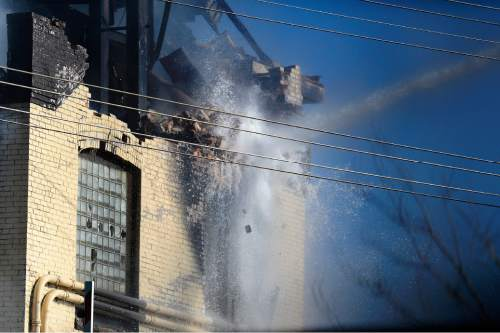 Scott Sommerdorf   |  The Salt Lake Tribune Firefighters water cannons break through the brick walls in order to have the water reach the fire inside the iconic Silver Cup fish feed factory in Murray, Saturday, November 7, 2015.
