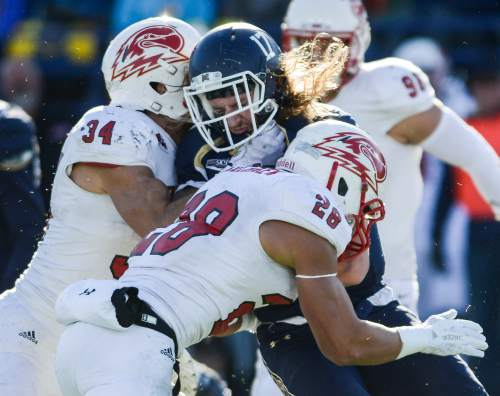 Montana State running back Chad Newell is stopped by Southern Utah linebacker Mike Needham, left, and defensive back Miles Killebrew during the first half of an NCAA college football game on Saturday, Nov. 7, 2015, in Bozeman, Mont. (Adrian Sanchez-Gonzalez/Bozeman Daily Chronicle via AP)