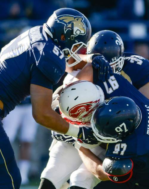 Southern Utah running back Malik Brown is tackled by Montana State defensive lineman Tyron Fa'anono, left, linebacker Blake Braun, center, and defensive tackle Connor Thomas during the first half of an NCAA college football game on Saturday, Nov. 7, 2015, in Bozeman, Mont. (Adrian Sanchez-Gonzalez/Bozeman Daily Chronicle via AP)