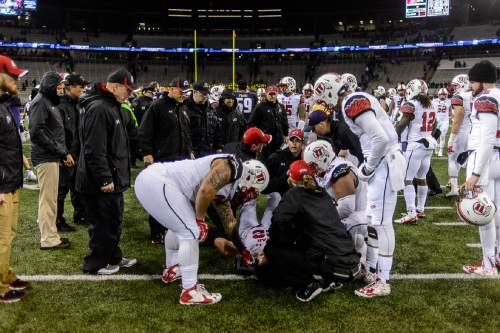 Trent Nelson  |  The Salt Lake Tribune Staff gather around Utah Utes quarterback Chase Hansen (22), who was injured on the last play of the game, as the University of Utah faces the University of Washington, NCAA football at Husky Stadium in Seattle, Saturday November 7, 2015.