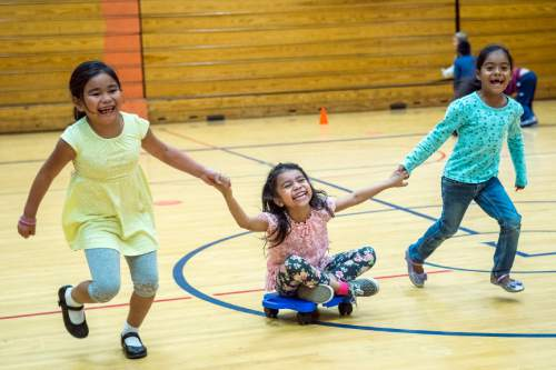 Chris Detrick  |  The Salt Lake Tribune First graders Alyani Phanthavong, Keren Soto and Genesis Orenday Camacho play in gym class at Lincoln Elementary School Tuesday October 6, 2015.
