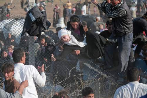 Syrian refugees are helped into Turkey after breaking the border fence and crossing from Syria in Akcakale, Sanliurfa province, southeastern Turkey,  Sunday, June 14, 2015.  The mass displacement of Syrians across the border into Turkey comes as Kurdish fighters and Islamic extremists clashed in nearby city of Tal Abyad. (AP Photo/Lefteris Pitarakis)