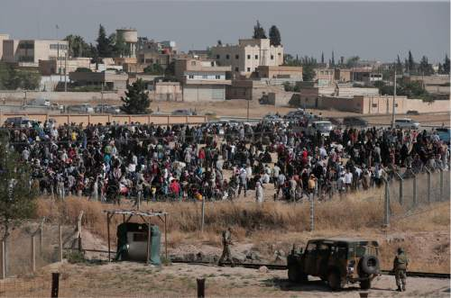 In this photo taken from the Turkish side of the border between Turkey and Syria, in Akcakale, Sanliurfa province, southeastern Turkey,  Turkish army, bottom, watch as Syrian refugees wait on the Syrian side of the border in order to cross, Saturday, June 13, 2015. Turkey's emergency management agency says more than 6,000 Syrians have crossed into Turkey in the past week, fleeing fighting between Islamic State militants and Kurdish forces near the northern Syrian city of Tel Abyad.  (AP Photo/Lefteris Pitarakis)
