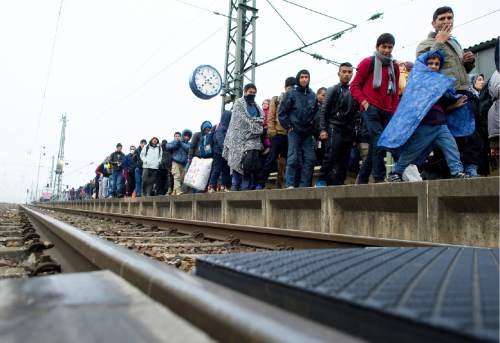 Migrants are on their way to board a train to Duesseldorf, Germany in Passau, near the Austrian border, southern Germany  Tuesday Nov. 3, 2015. German government parties discuss changes in the German migrant policy. (Angelika Warmuth/dpa via AP)