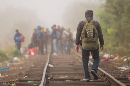 A man walks at the railway track after crossing the border line between Serbia and Hungary in Roszke, southern Hungary, Saturday, Sept. 12, 2015. Hundreds of thousands of Syrian refugees and others are still making their way slowly across Europe, seeking shelter where they can, taking a bus or a train where one is available, walking where it isn't. The latest string of walkers made their way Friday from the Hungarian border across Austria toward the capital, Vienna. (AP Photo/Christian Bruna)