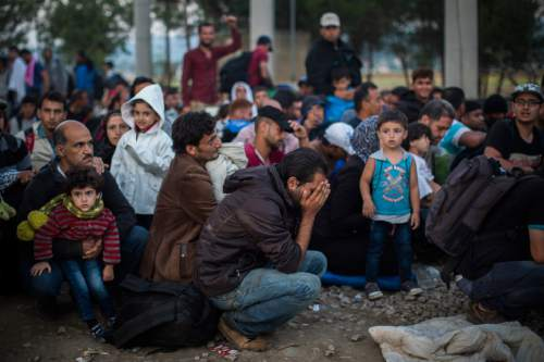 Syrian refugees wait near the border railway station of Idomeni, northern Greece, in order to be allowed by the Macedonian police to cross the border from Greece to Macedonia, Tuesday, Aug. 25, 2015. The U.N.'s refugee agency said it expects 3,000 people to cross Macedonia daily in the coming days. Greece has been overwhelmed this year by record numbers of migrants who have been arriving on a number of Greek islands.(AP Photo/Santi Palacios)