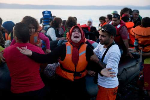 A woman reacts as she arrives aboard a dinghy after crossing from Turkey, to the island of Lesbos, Greece, on Saturday, Sept. 19, 2015. A girl about five years old died and at least 13 undocumented refugees and migrants were missing on Saturday after a boat transferring dozens of people from Turkey to Greece overturned off Lesbos island, Greek Coast Guard said. (AP Photo/Petros Giannakouris)