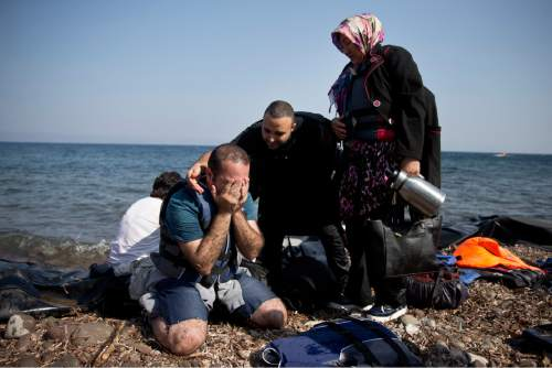Yshar, left,  a 36 year old musician from Iran reacts on the shores of the Greek island of Lesbos after crossing with others the Aegean Sea from Turkey on a inflatable dinghy, Monday,  Sept. 21, 2015. Greece's coast guard was searching Sunday for 26 migrants missing off the coast of the eastern Aegean island of Lesbos after the boat they were traveling in sank.(AP Photo/Petros Giannakouris)