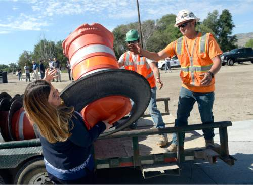 Al Hartmann  |  Tribune file photo The freewaylike interchange at Bangerter Highway and Redwood Road is now open.  Bluffdale Councilwoman Heather Pehrson throws some of the last of the orange construction barrels to workers to open the intersection Thursday, July 16.