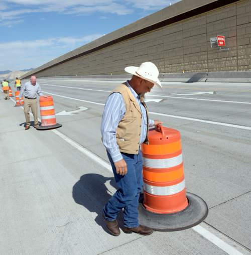 Al Hartmann  |  The Salt Lake Tribune The freewaylike interchange at Bangerter Highway and Redwood Road is now open. Bluffdale Councilman Ty Nielsen, right, and Sen. Howard Stephenson, R-Draper, helped workers remove the last of the orange construction barrels on Thursday, July 16.