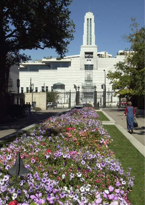 Al Hartmann  |  Tribune File Photo  Due to a warm fall flowers are still in bloom at Temple Square.  The LDS onference Center is the tower in back. Oct. 2, 2003.