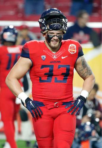FILe - In this Dec. 31, 2014, file photo, Arizona's Scooby Wright III smiles as he walks on the field prior to the Fiesta Bowl NCAA college football game against Boise State in Glendale, Ariz. Arizona returns most of its skill players on offense and All-American Scooby Wright is back to lead the defense. (AP Photo/Ross D. Franklin, File)