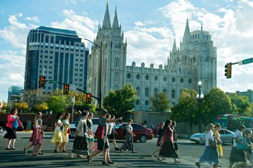 Lennie Mahler  |  The Salt Lake Tribune Women pass by the LDS Temple on their way to the first session of the 185th LDS General Conference on Saturday, in Salt Lake City. The session is for all LDS women and girls eight years or older.