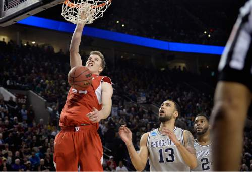 "Scott Sommerdorf   |  The Salt Lake Tribune Utah Utes forward Jakob Poeltl (42) dunks over Georgetown Hoyas forward Paul White (13) during second half play. Utah defeated Georgetown 75-64 to advance to the ""Sweet Sixteen"", Saturday, March 21, 2015."