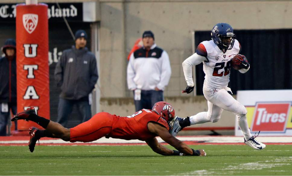 Arizona running back Nick Wilson (28) outruns Utah defensive end Nate Orchard (8) in the second quarter during an NCAA college football game Saturday, Nov. 22, 2014, in Salt Lake City. (AP Photo/Rick Bowmer)
