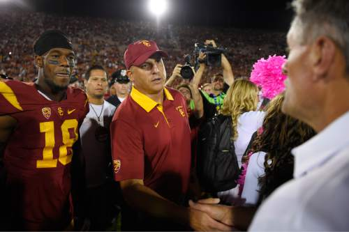 Southern California head coach Clay Helton, center, shakes hand with Utah head coach Kyle Whittingham, right, as wide receiver Ajene Harris looks on after an NCAA college football game, Saturday, Oct. 24, 2015, in Los Angeles. Southern California won 42-24. (AP Photo/Mark J. Terrill)