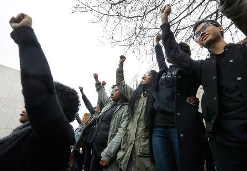 Students at Boston College raise their arms during a solidarity demonstration on the school's campus, Thursday, Nov. 12, 2015, in Newton, Mass. The protest was among numerous campus actions around the country following the racially charged strife at the University of Missouri. (AP Photo/Steven Senne)