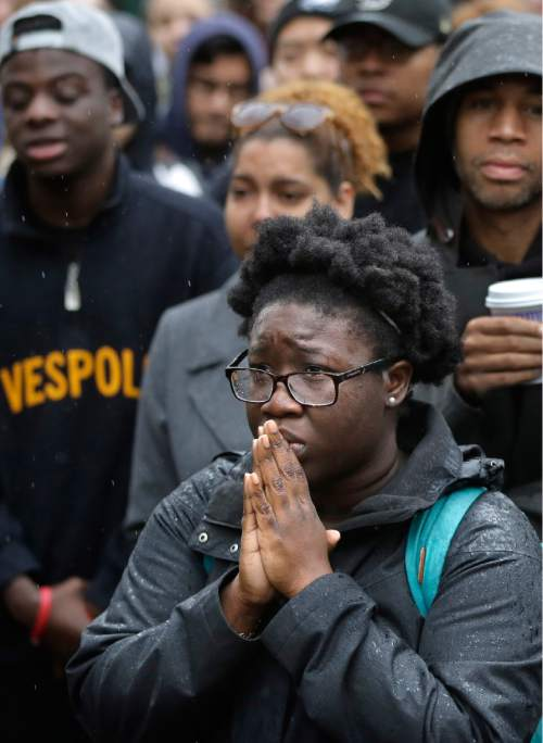 Boston College student Akosua Opokua-Achampong, of Lake Hopatcong, N.J., places her hands together during a solidarity demonstration on the school's campus, Thursday, Nov. 12, 2015, in Newton, Mass. The protest was among numerous campus actions around the country following the racially charged strife at the University of Missouri. (AP Photo/Steven Senne)