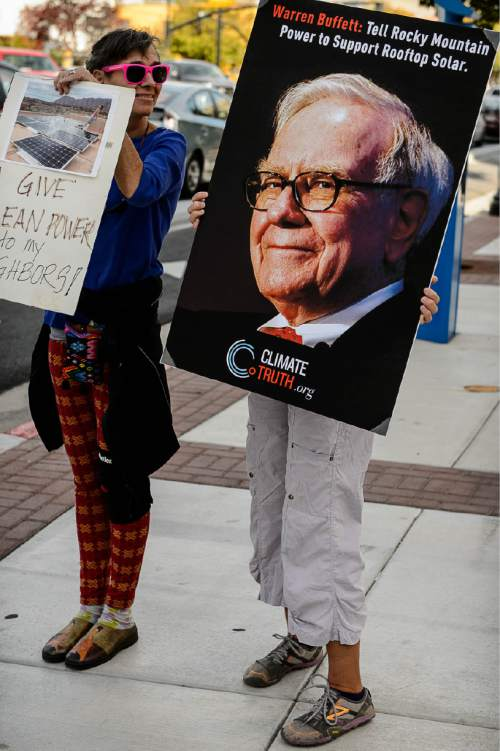 Trent Nelson  |  The Salt Lake Tribune Women hold signs as clean energy advocates gather outside the Utah Public Service Commission (PSC) in Salt Lake City, Thursday October 8, 2015, before a hearing on fees levied by utilities on rooftop solar users.