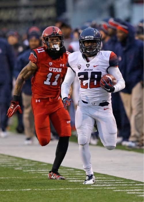 Utah defensive back Davion Orphey (11) pursues Arizona running back Nick Wilson (28) in the first half of an NCAA college football game Saturday, Nov. 22, 2014, in Salt Lake City. Arizona won 42-10. (AP Photo/Rick Bowmer)