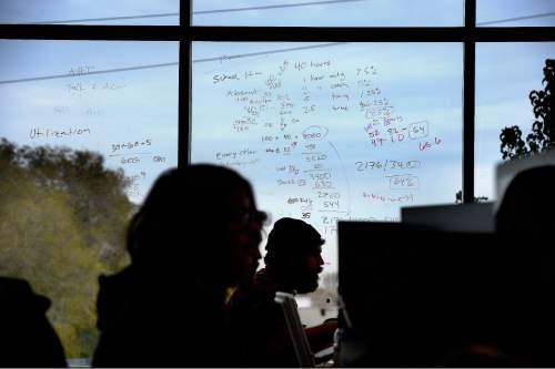 Scott Sommerdorf   |  The Salt Lake Tribune Workers at Thumbtack in Sandy take calls beneath a window used for doodling concepts, Wednesday, October 28, 2015.