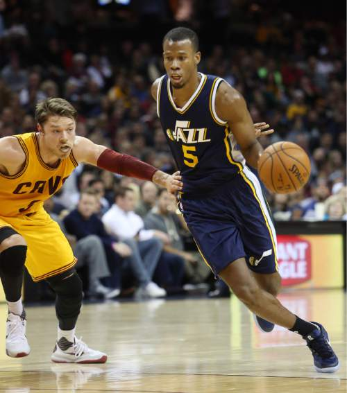 Utah Jazz guard Rodney Hood (5) drives around Cleveland Cavaliers guard Matthew Dellavedova (8) during the first half of an NBA basketball game Tuesday, Nov. 10, 2015, in Cleveland. (AP Photo/Ron Schwane)