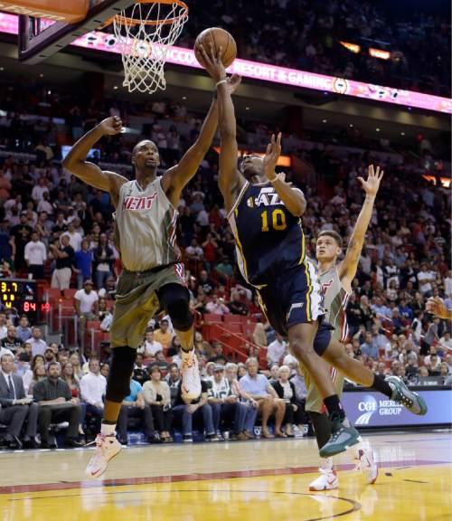 Utah Jazz guard Alec Burks (10) goes to the basket against Miami Heat forward Chris Bosh (1) in the second half of an NBA basketball game, Thursday, Nov. 12, 2015, in Miami. The Heat won 92-91. (AP Photo/Alan Diaz)