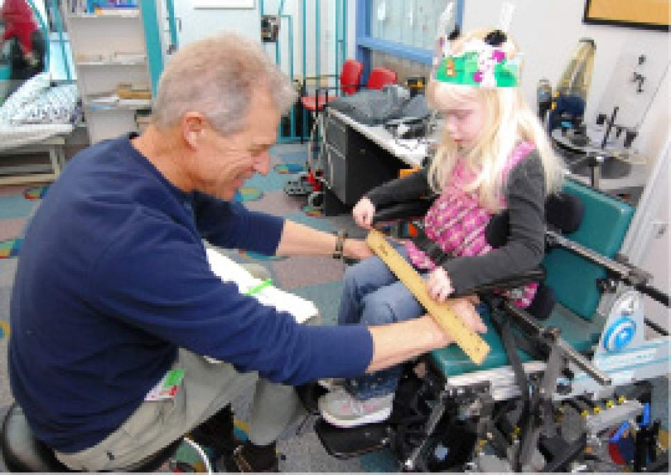 Courtesy  |  Shriners Hospital for Children Ken Kazole, occupational therapist and seating specialist, helps a young hospital patient as part of a wheelchair & seating program at Shriners Hospitals for Children in Salt Lake City.