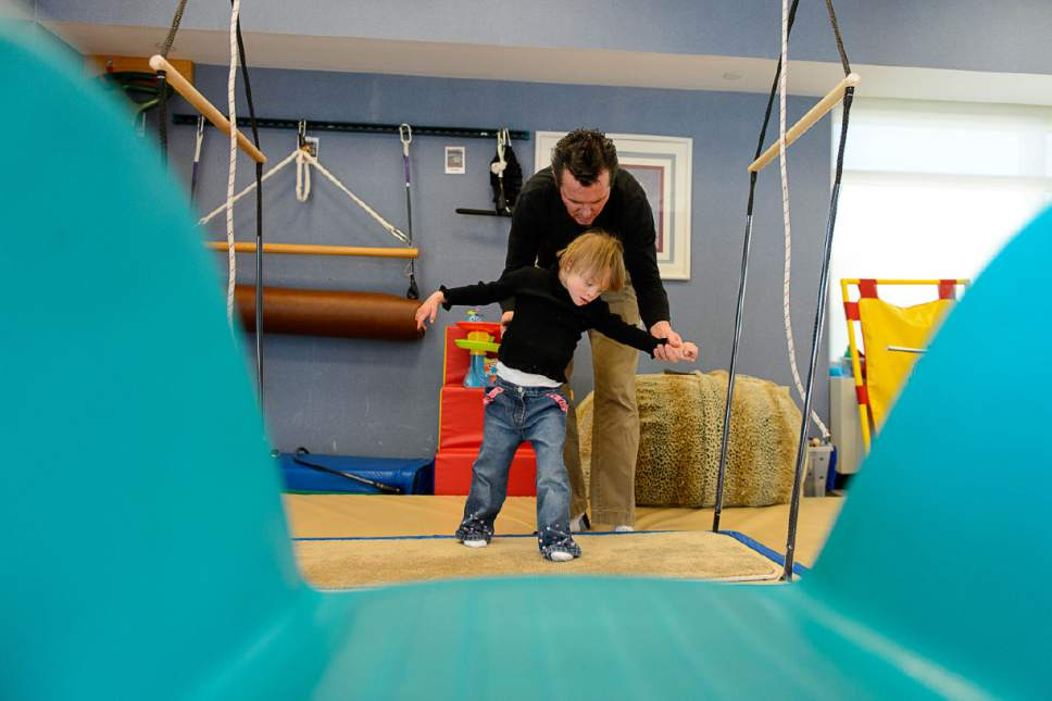 Trent Nelson  |  The Salt Lake Tribune Mark Lange, rear, works with Nevaeh Fairclough at Shriners Hospital in Salt Lake City, Wednesday November 11, 2015.