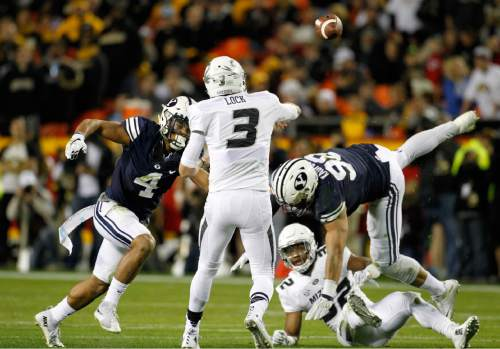 Missouri quarterback Drew Lock (3) passes the ball as he is pressured by BYU linebacker Fred Warner (4) and BYU defensive lineman Bronson Kaufusi (90) in the first half of a college football game at Arrowhead Stadium, Saturday, Nov. 14, 2015, in Kansas City, Mo. (AP Photo/Colin E. Braley)