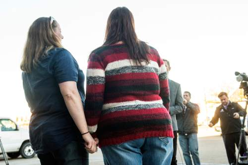 Chris Detrick  |  The Salt Lake Tribune April Hoagland and Beckie Peirce hold hands during a press conference outside of the Juvenile Court in Price, Utah Friday November 13, 2015. Seventh District Juvenile Judge Scott Johansen has amended an order to remove a 9-month-old girl from the Price home of her same-sex foster parents and has instead scheduled a hearing on the matter.