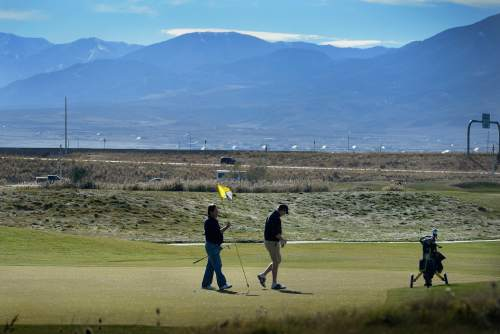Scott Sommerdorf   |  The Salt Lake Tribune Golfers play on Wingpointe's 9th green, Sunday, November 15, 2015. A few golfers made off with flag sticks, and tee box markers as souvenirs on the course's final day. The Wingpointe Golf Course will close at the end of business on Sunday, November 15. The golf course property will be returned to the Salt Lake City Department of Airports by the end of December 2015.