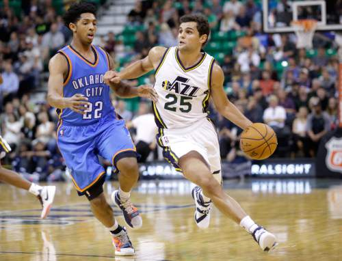FILE - This Tuesday, Oct. 20, 2015, file photo, shows Utah Jazz guard Raul Neto (25) driving around Oklahoma City Thunder guard Cameron Payne (22) during the second quarter of an NBA preseason basketball game, in Salt Lake City. The loss of Dante Exum to injury sent ripples throughout the Jazz lineup that will be felt on both sides of the ball. The opportunities for Trey Burke and Raul Neto have grown exponentially especially after Bryce Cotton was released last week. (AP Photo/Rick Bowmer, File)