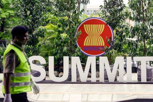 A security guard walks past the ASEAN logo at the 27th Association of Southeast Asian Nations (ASEAN) summit in Kuala Lumpur, Malaysia, Thursday, Nov. 19, 2015. The ASEAN summit and relating meetings are held in Malaysia on Nov. 18-22. (AP Photo/Joshua Paul)