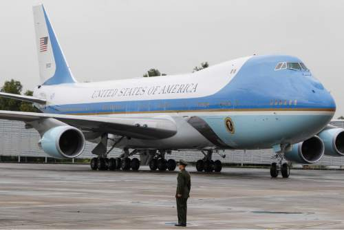 A U.S. military personnel stands in attention as the Air Force One arrives at the Subang Airbase in Kuala Lumpur, Malaysia, Friday, Nov. 20, 2015. Obama is traveling to Malaysia where he will join leaders from Southeast Asia to discuss trade and economic issues, and terrorism and disputes over the South China Sea. (AP Photo/Joshua Paul)