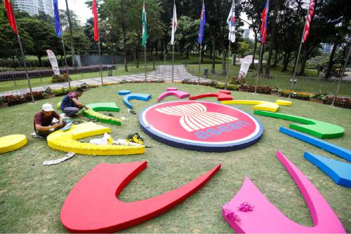 Workers add final touches to the ASEAN logo at the 27th Association of Southeast Asian Nations (ASEAN) summit in Kuala Lumpur, Malaysia, Thursday, Nov. 19, 2015. The ASEAN summit and relating meeting are held in Malaysia on Nov. 18-22. (AP Photo/Joshua Paul)