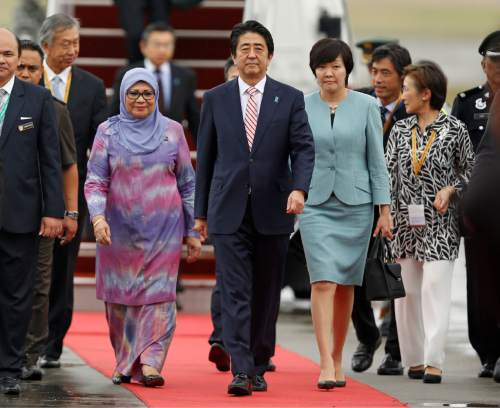 Japanese Prime Minister Shinzo Abe, center, and his wife Akie Abe, right, walk as they arrive for the 27th Association of Southeast Asian Nations (ASEAN) summit, in Sepang, Malaysia, Friday, Nov. 20, 2015. (AP Photo/Lai Seng Sin)