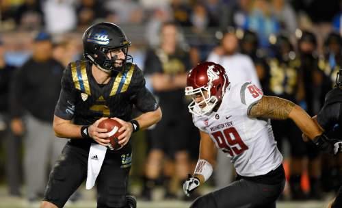 UCLA quarterback Josh Rosen, left, tries to get away from Washington State defensive lineman Darryl Paulo during the first half of an NCAA college football game, Saturday, Nov. 14, 2015, in Pasadena, Calif. (AP Photo/Mark J. Terrill)