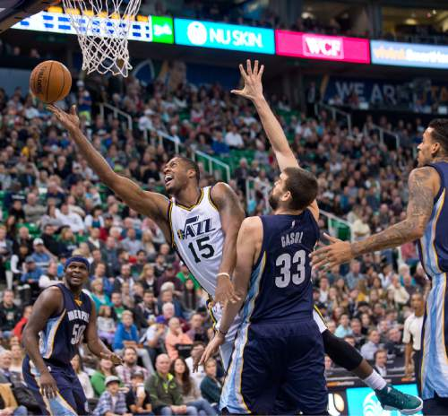 Lennie Mahler  |  The Salt Lake Tribune  Utah forward Derrick Favors scoops a shot in past Memphis center Marc Gasol in the first half of a game against the Memphis Grizzlies at Vivint Smart Home Arena on Saturday, Nov. 7, 2015.