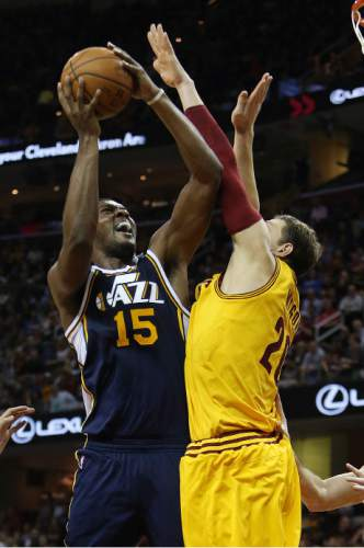 Utah Jazz forward Derrick Favors (15) shoots against Cleveland Cavaliers center Timofey Mozgov (20) during the second half of an NBA basketball game Tuesday, Nov. 10, 2015, in Cleveland. The Cavaliers won 118-114. (AP Photo/Ron Schwane)
