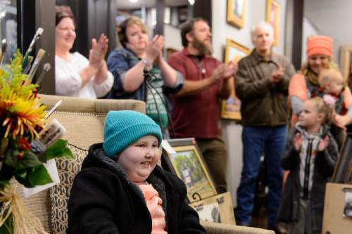 Trent Nelson  |  The Salt Lake Tribune People applaud BayLee Parks, a young girl and artist who has been battling cancer for 7 years, at the Illume Gallery in Salt Lake City, Thursday November 12, 2015. Dozens of people attended the show of Parks' paintings, including many artists, who brought paint brushes as gifts to Parks. Her paintings sold out.