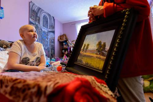 Trent Nelson  |  The Salt Lake Tribune BayLee Parks in her Midvale bedroom with one of her paintings, held by her mother, Shellie Bassett, Nov. 17. Parks, 17, is getting her affairs in order. She was diagnosed at age 10 with Medulloblastoma and rather than undergo yet another round of chemotherapy, she's decided to stop treatment.
