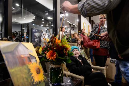 Trent Nelson  |  The Salt Lake Tribune Artist Thomas Howard puts a paintbrush into a bouquet for BayLee Parks, a young girl and artist who has been battling cancer for 7 years, at the Illume Gallery in Salt Lake City, Thursday November 12, 2015. Dozens of people attended the show of Parks' paintings, including many artists, who brought paint brushes as gifts to Parks. Her paintings sold out.