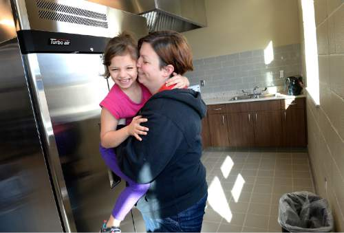 Scott Sommerdorf   |  The Salt Lake Tribune Jennifer Carter holds her 7 year old daughter Ryle as they react to getting a tour of one of the kitchens that residents at The Road Home's new Community Winter Shelter will be able to use to cook for their families, Wednesday, November 25, 2015.