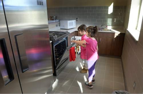 Scott Sommerdorf   |  The Salt Lake Tribune Sisters Ryle Carter (7), left, and Starlet (5), right were intrigued by the oven as they react to getting a tour of one of the kitchens that residents at The Road Home's new Community Winter Shelter will be able to use to cook for their families, Wednesday, November 25, 2015.