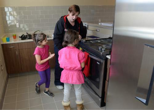 Scott Sommerdorf   |  The Salt Lake Tribune Jennifer Carter, with her 7 year old daughter Ryle and 5 year old daughter Starlet, react to getting a tour of one of the kitchens that residents at The Road Home's new Community Winter Shelter will be able to use to cook for their families, Wednesday, November 25, 2015.