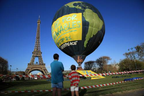 Boys look at a hot air balloon of the environmental group Greenpeace, near the Eiffel Tower ahead of the 2015 Paris Climate Conference, in Paris, Saturday, Nov. 28, 2015. The conference with more than 100 heads of state is scheduled to start on Nov.30. (AP Photo/Thibault Camus)