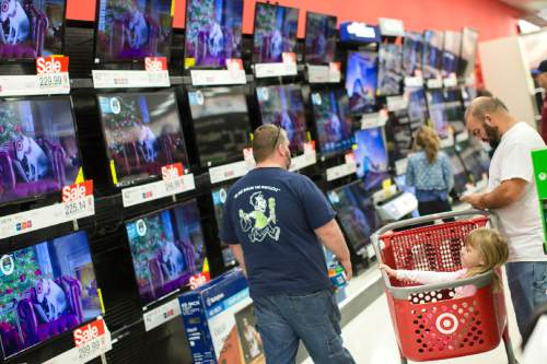 A child rests in a shopping cart in the electronics section against a backdrop of televisions at a Target store, Friday, Nov. 27, 2015, in Newport, Ky. (AP Photo/John Minchillo)