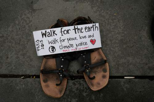 "A message saying 'Walk for the earth' is seen on a pair of shoes, as hundreds of pairs of shoes are displayed at the place de la Republique, in Paris, as part of a symbolic and peaceful rally called by the NGO Avaaz ""Paris sets off for climate"", Sunday, Nov. 29, 2015.  More than 140 world leaders are gathering around Paris for high-stakes climate talks that start Monday, and activists are holding marches and protests around the world to urge them to reach a strong agreement to slow global warming. (AP Photo/Laurent Cipriani)"